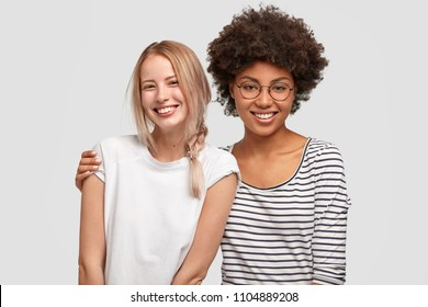 Two beautiful mutiethnic delighted women have good relationship and truthful friendship, embarce each other and smile gladfully, happy to meet after long time. Interracial friendship concept