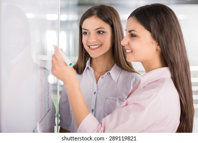 Two beautiful office workers drawing business strategy on flip chart.