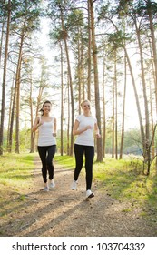 Two beautiful runnersjogging in the sunny forest