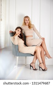 Two beautiful sexy woman blond and brunette hair wear same dress beige and blouse and skirt fashion catalog clothes casual street style model designer white room background fall spring collection.