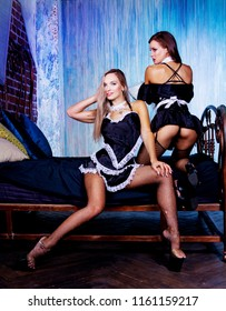 two beautiful sexy women dressed as maids in the bedroom at home