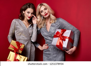 Two beautiful sexy young woman bright evening make-up red lips long fluffy eyelashes hold gift box holiday New Year  joy fun happy merry Christmas Eve party celebration St. Valentine's Day girlfriend.