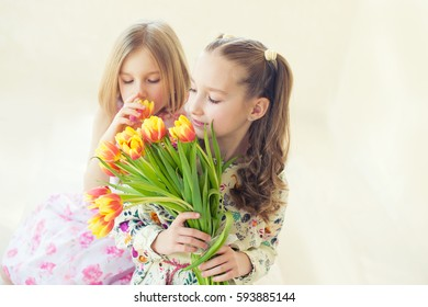 Two beautiful sisters girls loving each other sit in room enjoying relations, sun and flowers in hands, ready to celebrate spring March holiday or birthday.