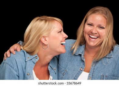 Two Beautiful Sisters Laughing Isolated on a Black Background.