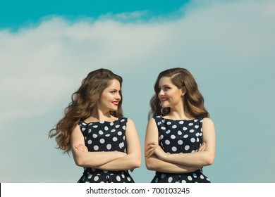 Two beautiful sisters twin girls in identical dresses, with makeup and hairdo on blue sky background