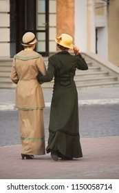 Two beautiful slim girls in costumes. walking along cobbled street of old european town. Old-fashioned retro novel's heroines.