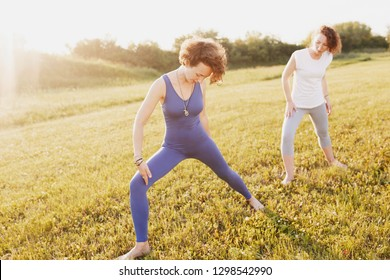 Two beautiful slim healthy young women in sportswear doing the pose of a hero yoga asana on a green lawn in a park on a sunny summer day. Healthy slim body concept. Advertising space