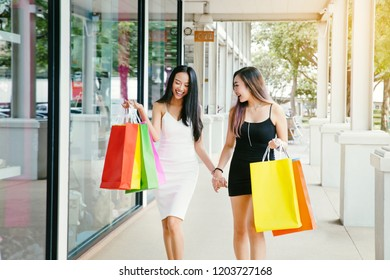 Two beautiful smiling asian girls with shopping bags in  city street.Sale.black friday