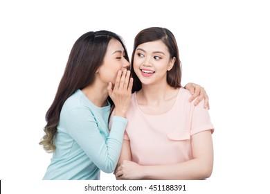 Two beautiful smiling girls sharing a secret