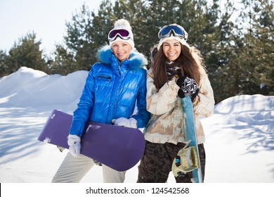 Two beautiful smiling girls with snowboards standing outside, sunny winter day