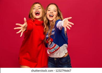 Two beautiful smiling gorgeous girls looking at camera. Women standing in stylish winter warm sweaters on red background. Christmas, x-mas, concept.