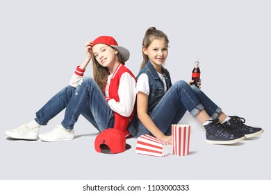 Two beautiful smiling teen girlfriends sitting on a gray background. friendship, fashion, summer and teens concept. Space for text.