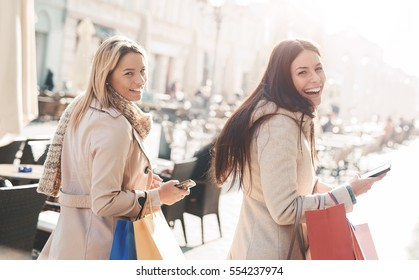 Two beautiful smiling women walking down the street on a sunny day after good shopping. Consumerism, lifestyle concept
