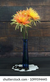 Two beautiful spider mums in a blue vase against a rustic wooden wall background.  Antique keys sit at the base on an ecru doily.