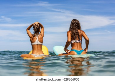 Two beautiful sporty surfing girl in sexy bikini sit on a big longboard surf surfboard board and wait for big wave on sunrise or sunset in the ocean. Modern active sport lifestyle and summer vacation.