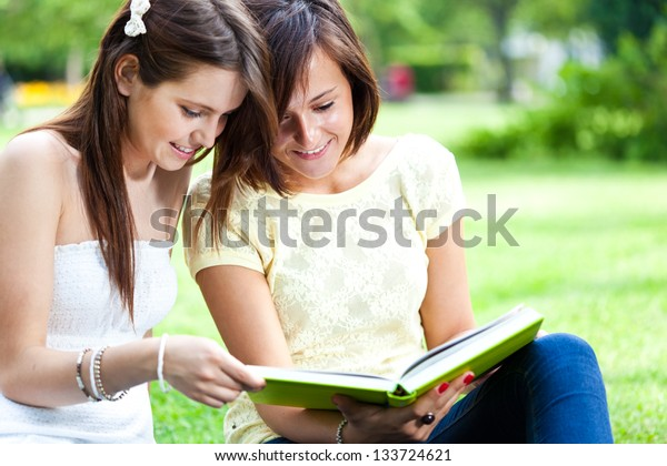 Two beautiful students reading a book on the grass