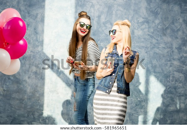 Two beautiful stylish friends using phone on the blue wall background