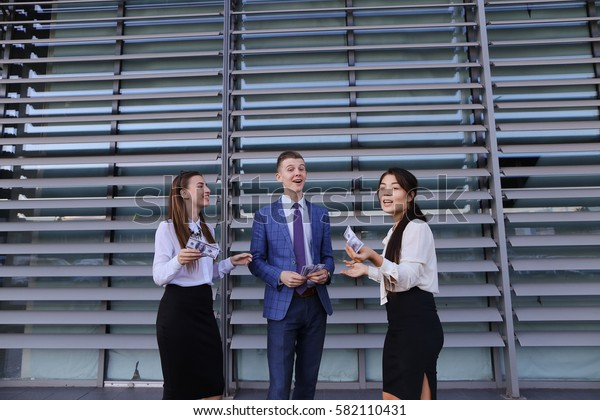 Two beautiful successful young women, business woman and confident young guy male entrepreneur, held personality, hold in hands money, dollar and scattered, communicate with each other, posing and