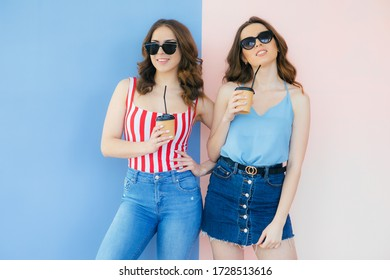 Two beautiful summer girls 20s with different color of skin in dresses smiling at camera and showing paper cups with takeaway coffee isolated over color background
