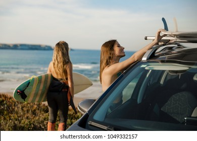 Two beautiful surfer girls near the coastline with her car, and getting ready for surfing