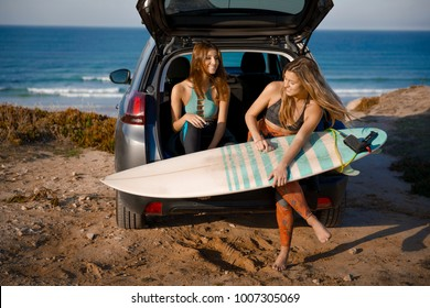 Two beautiful surfer girls sitting on the trunk of car getting ready for surfing