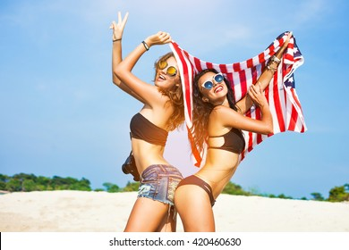 Two beautiful tanned fun hipster girls on the beach, blonde and brunette standing back to back and holding an American flag, old style, laugh, smile relax on a tropical island sexy bikini denim shorts
