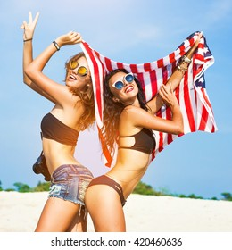 Two beautiful tanned fun hipster girls on the beach, blonde and brunette holding an American flag, old style, laugh, relax on a tropical island, sexy bikini, denim shorts, fashion sunglasses, square
