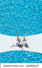 Two beautiful tanned sporty slim women relaxing in swimming pool spa.
