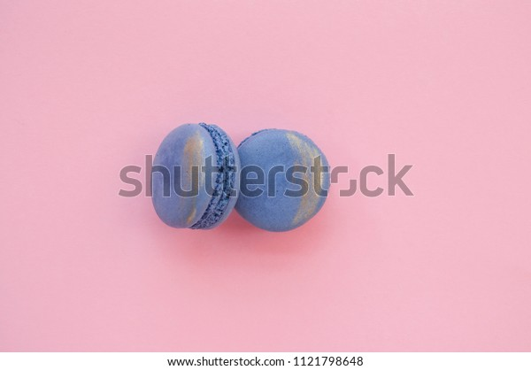 Two beautiful and tasty violet color macaroons with golden stroke on pink background with text space.
