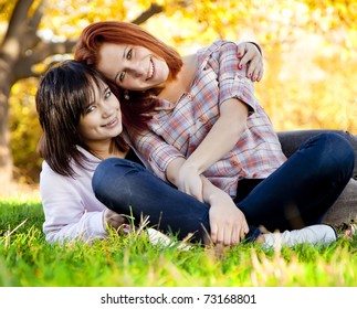 Two beautiful teen girl at green grass in the park.