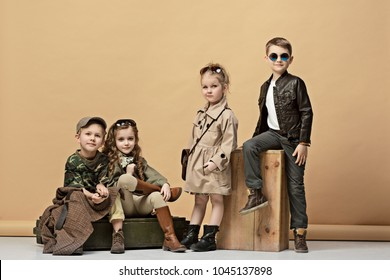 Two beautiful teen girls and boys on a pastel studio background. Stylish young teen girls posing at studio. Safari style. Classic style. Teen and kids fashion concept. children's fasion concept