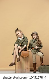 Two beautiful teen girls sitting on a pastel studio background. Stylish young teen girls posing at studio. Safari style. Classic style. Teen and kids fashion concept. children's fasion concept