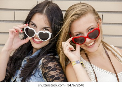 Two beautiful teenage girl wearing funny sun glasses