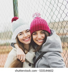 Two beautiful teenage girlfriends hugging and smiling outdoors in winter, wearing coats and knit beanie hats. Two young female friends portrait closeup. Retouched, natural light.
