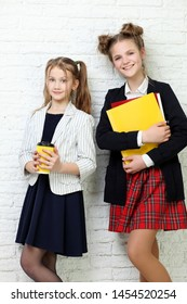 two beautiful teenage girls holding books and smiling
