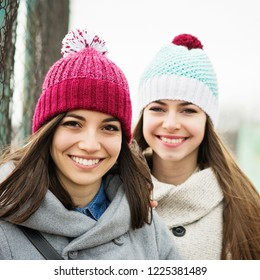 Two beautiful teenage girls in winter, smiling, wearing knitted hats. Closeup, mild retouch. Square format image.