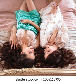 Two beautiful twins young women in a lacy sleepwear. Bride and braidsmaid together in a morning.
