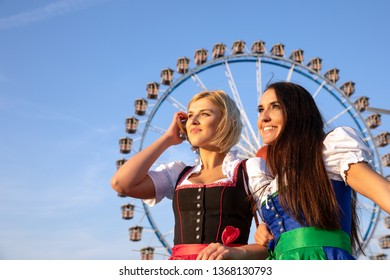 two beautiful woman in a dirndl dress are doing oktoberfest in munich. behind them are a huge ferris wheel and in her hands a colerful ballon