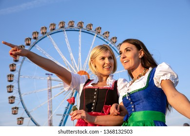 two beautiful woman in a dirndl dress are doing oktoberfest and having fun. behind them you can see a huge ferris wheel. in her hand a colerful balloon