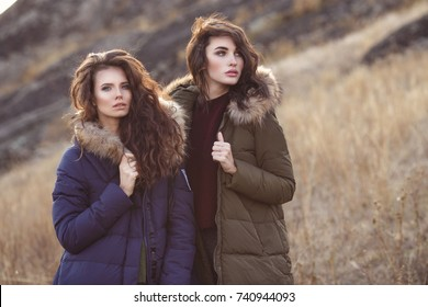 Two beautiful woman in fashion winter clothes outside. Trendy autumn and winter clothes. Down jacket.