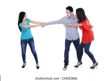 Two beautiful woman fighting over handsome man, isolated over white background
