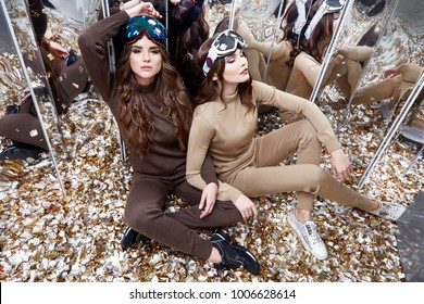 Two beautiful woman friends sit on the floor mirror sequins party fun celebrate new year holiday wear casual knitted wool suit ski goggles sport shoes extreme winter game brunette hair heath lifestyle