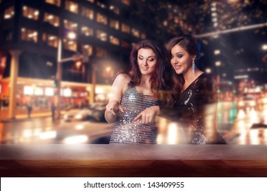 Two beautiful woman looking in the shopwindow on the night city street