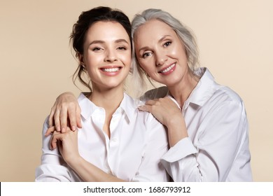 Two beautiful woman in white shirt hug face forward portrait. Studio headshot of toothy smiling grandmother and granddaughter, senior mother and daughter, elderly and young sister. Happy family