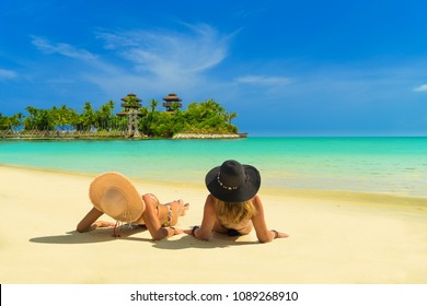 Two beautiful women in bikini sunbathing at the seaside on Sentosa island in Singapore