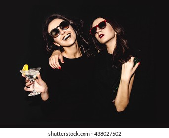 Two beautiful women in black night fashion dress posing isolated on a black background. Pretty brunette girl friends twins having fun drinking cocktails. Singing and dancing. Bottle glass of alcohol.