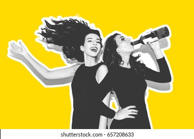 Two beautiful women in black night fashion dress posing isolated on a white gray background. Pretty brunette girl friends twins having fun drinking cocktails. Singing and dancing. Festive mood. Inside