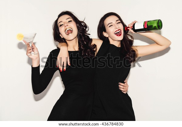 Two beautiful women in black night fashion dress posing isolated on a white gray background. Pretty brunette girl friends twins having fun drinking cocktails. Singing and dancing. Bottle of wine.
