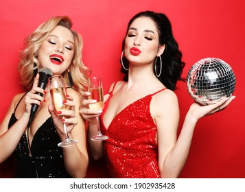 Two beautiful women, blonde and brunette wearing dresses, sing with a microphone, holding disco balls and glass of wine, Party and celebration. Joy and happiness. Gorgeous hairstyles and makeup.