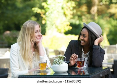 Two beautiful women drinking tea outdoors